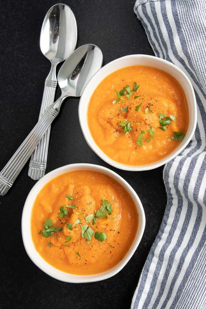Two bowls of bright orange carrot ginger soup sprinkled with parsley