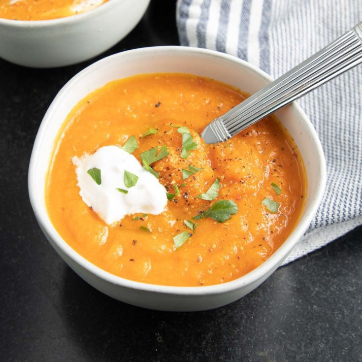 Bowl of carrot ginger soup with parsley and cashew cream