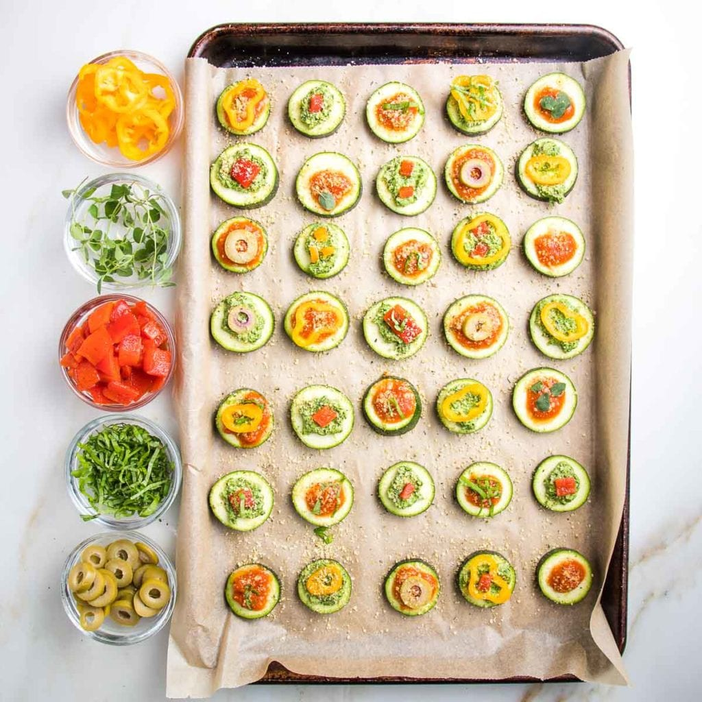 Large rimmed baking tray, lined with parchment and covered with zucchini rounds that have either marinara or pesto and then topped with veggies.  Small glass dishes on the side with toppings: yellow peppers, fresh basil, roasted red peppers, fresh oregano, sliced olives.