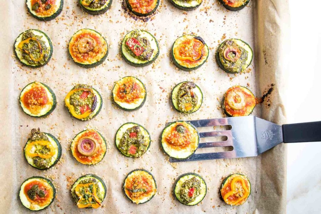 Zucchini Pizza Bites topped with pesto or marinara and colorful toppings...on a rimmed baking sheet with unbleached parchment. A small spatula is offloading the vegan appetizers.