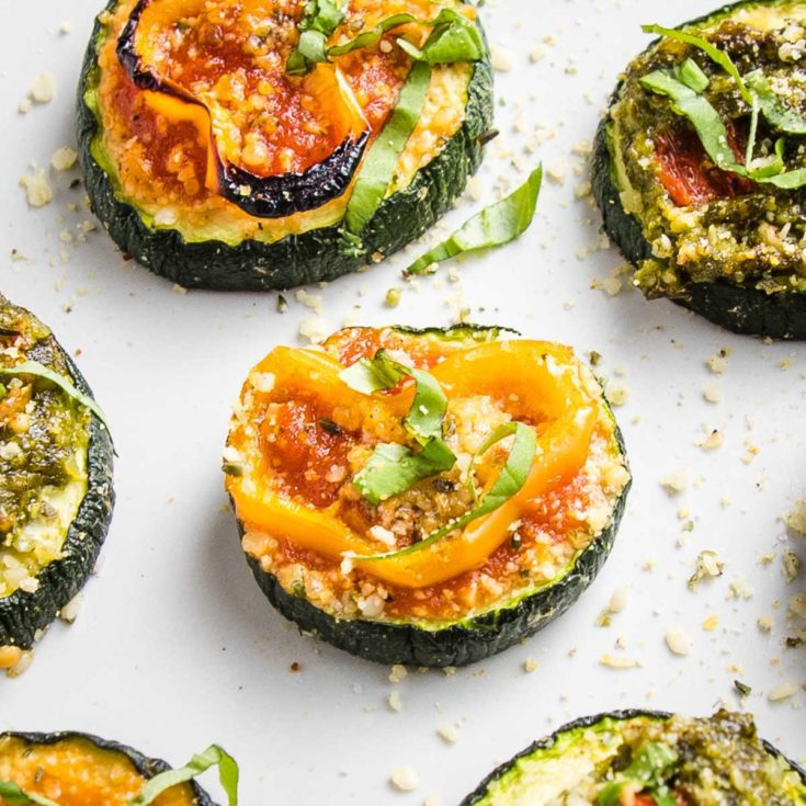 Close up of a few sliced zucchini pizza bites on a white tray. One has red sauce, a sliced yellow pepper and some fesh basil, another has pesto and roasted red pepper.