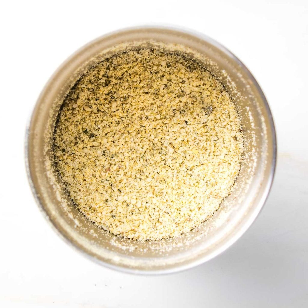 Small stainless steel bowl of spice grinder with vegan parmesan.