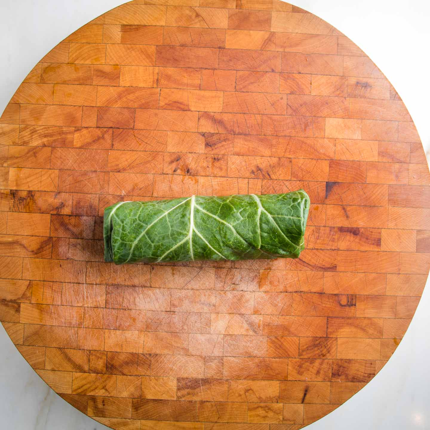 collard green wrap on top of round wooden cutting board.
