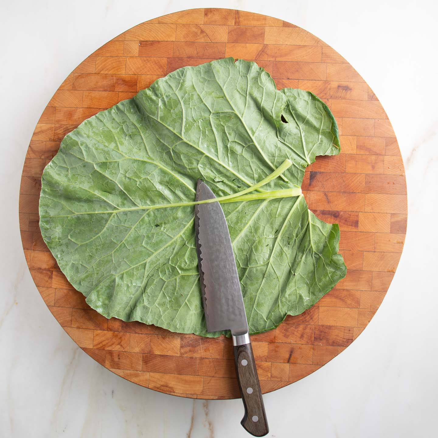 Round wooden cutting board with a large leaf of collard green.  Knife is cutting along the firm stem (backbone) to make the collard pliable for wrapping.