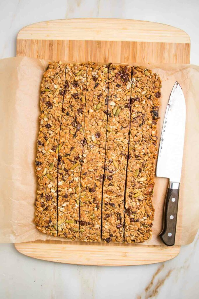 slab of granola bars on a piece of parchment that's on a cutting board.  They are cut into long strips with a sharp knife on the edge of the board.
