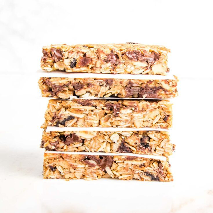 A stack of crunchy granola bars, with parchment paper in between layers.