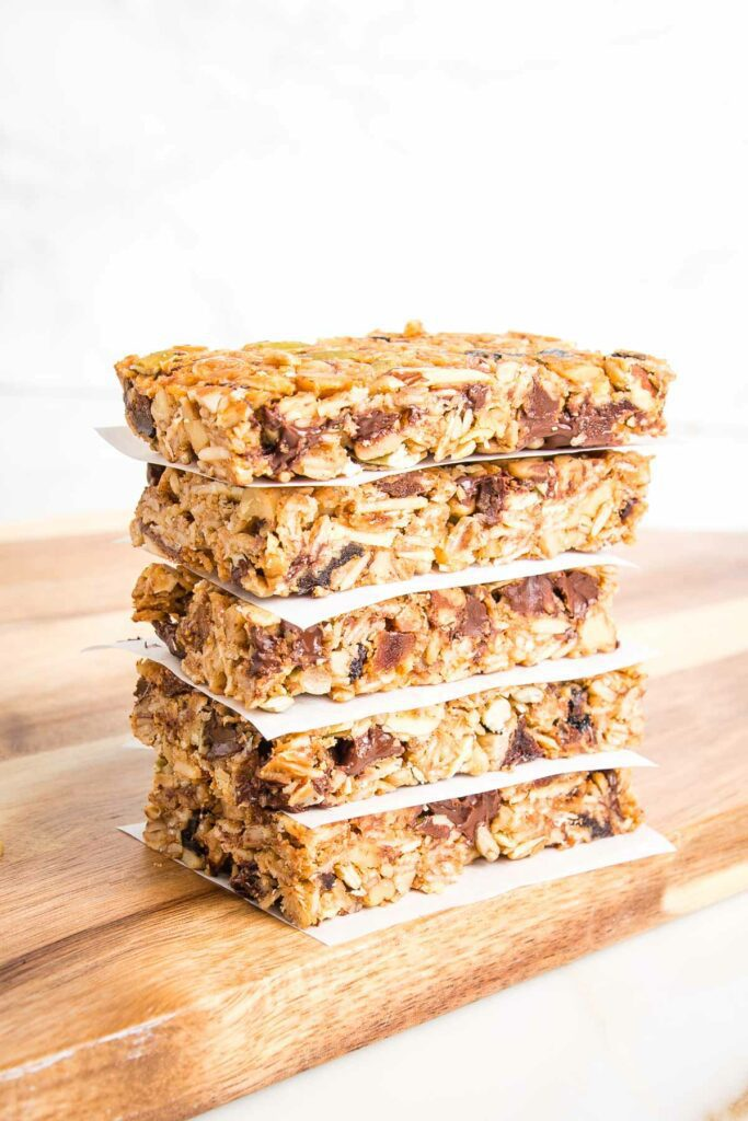 Stack of crunchy granola bars shown from the side with parchment in between layers.