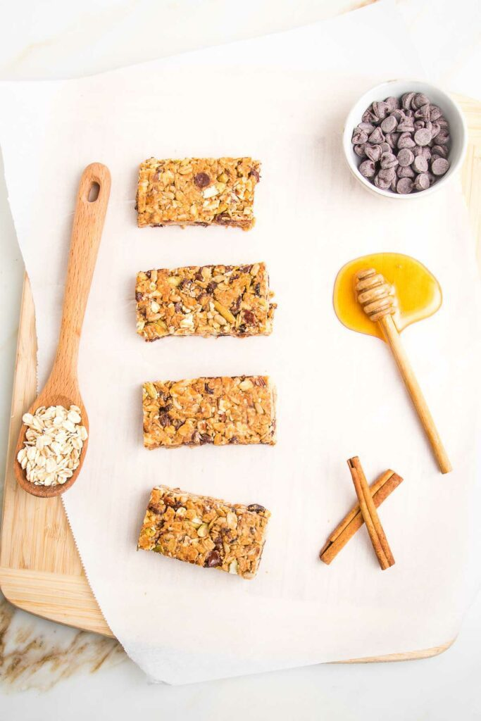 4 crunchy granola bars lined up on a piece of parchments. There is a spoon full of oats, a puddle of honey, a dish of chocolate chips and two cinnamon sticks.