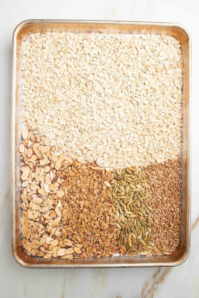 Large rimmed baking tray with oats, sliced almonds, chopped walnuts, sesame seeds and pumpkin seeds