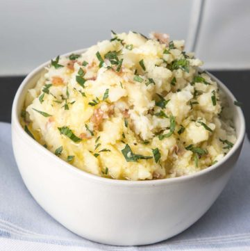 Bowl of mashed potatoes with chopped greens on top.