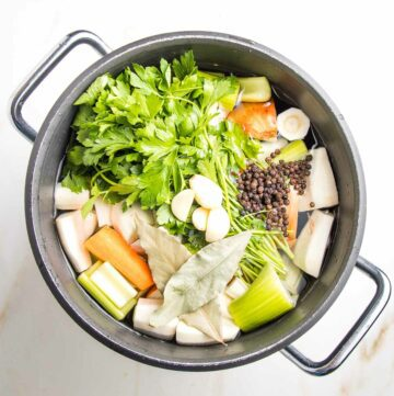 Stock pot filled with water and veggies: a bunch of parsley, carrots, onions, celery, parsnips, bay leaves and whole peppercorns.