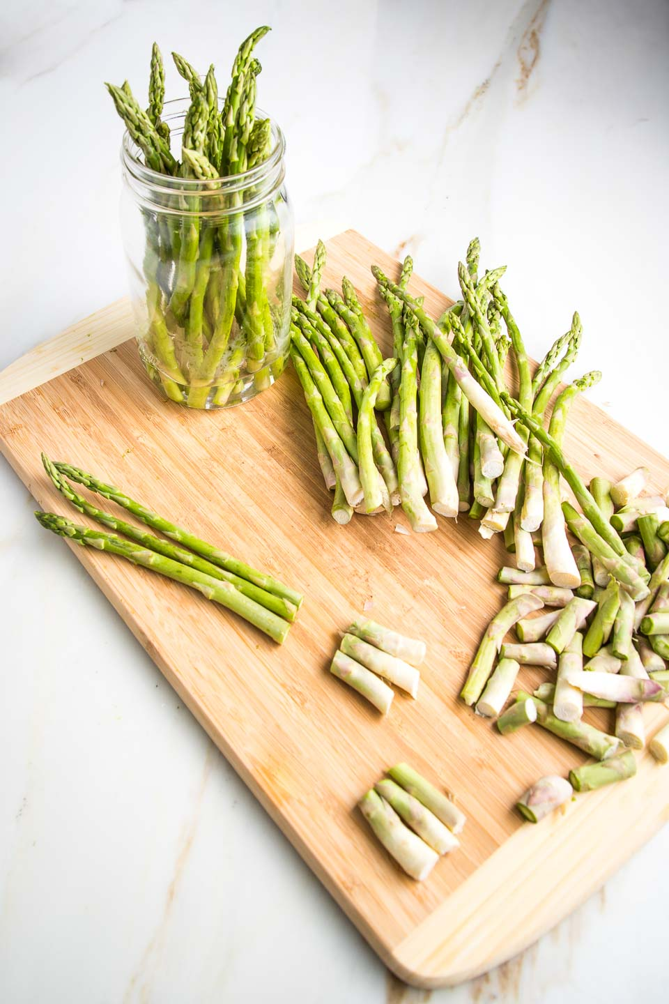 Cutting board with a bunch of asparagus, showing to trim the bottom off. A glass mason jar with already trimmed asparagus standing upright in an inch of water.