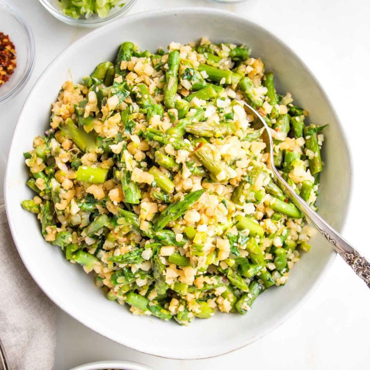 Large white serving bowl filled with Cauliflower rice and asparagus.