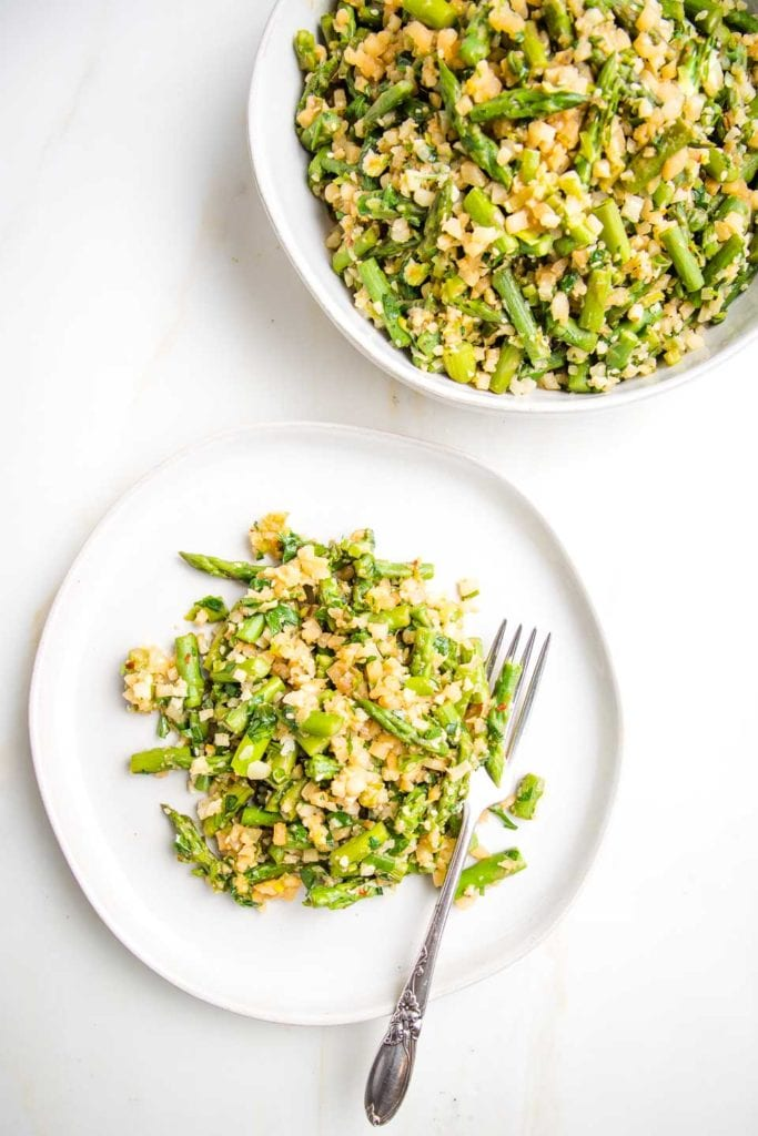 serving bowl filled with cauliflower rice with asparagus and a round white plate with a serving of same side dish with a a fork.