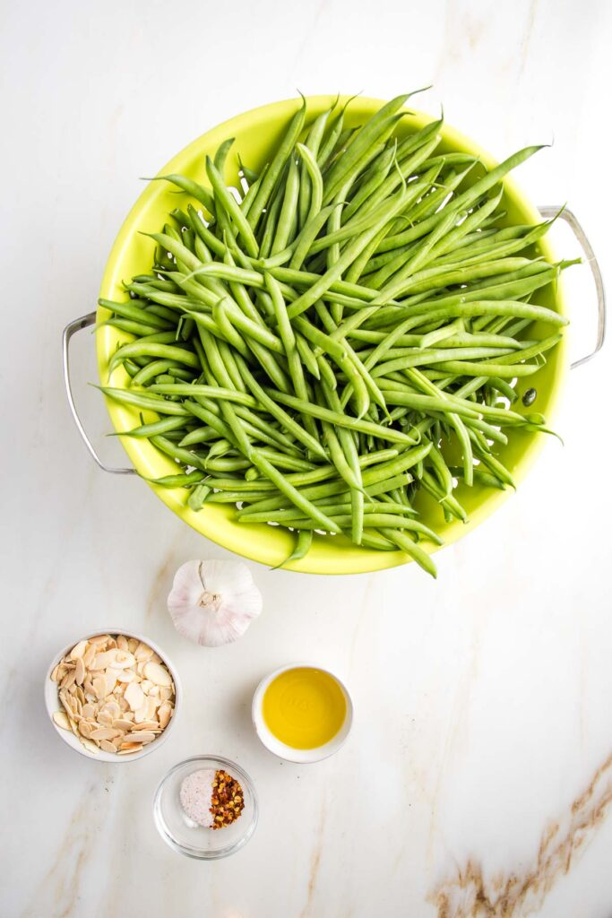 Lime green colander filled with green beans, a head of garlic, small bowls filled with olive oil, sliced almonds, salt and crushed red pepper
