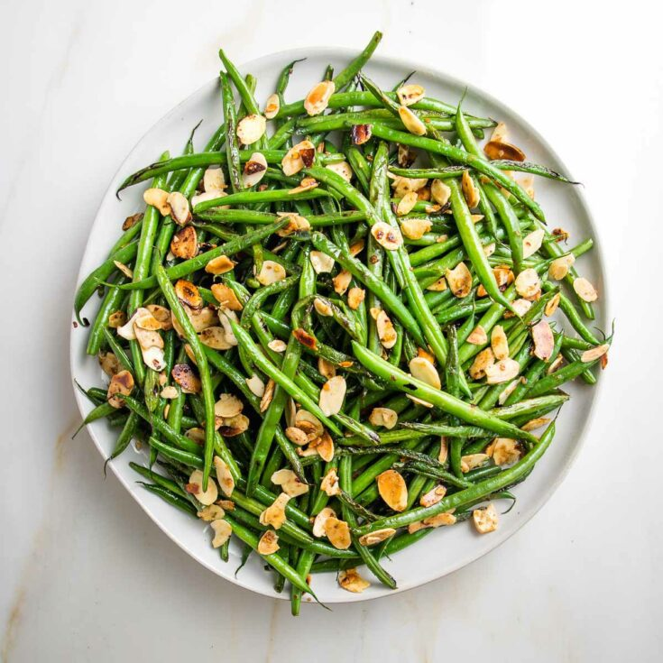 White plate with rim, filled with french cut green beans already cooked with sliced almonds.