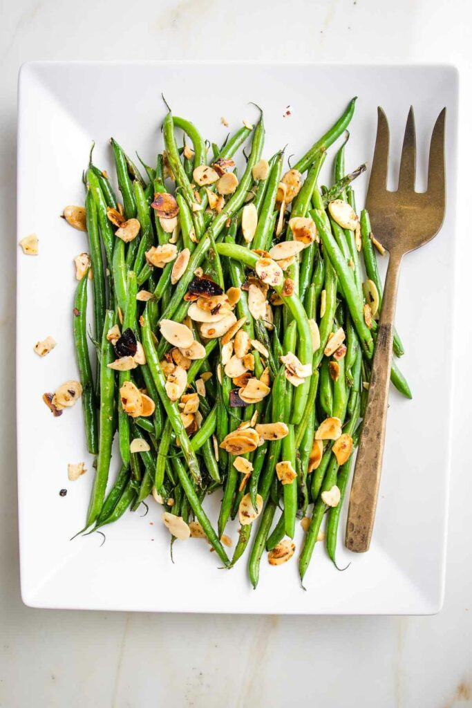 White rectangular dish with Green beans almondine. Bright green string beans loaded with sliced almonds and crushed red pepper with a bronze colored serving fork.