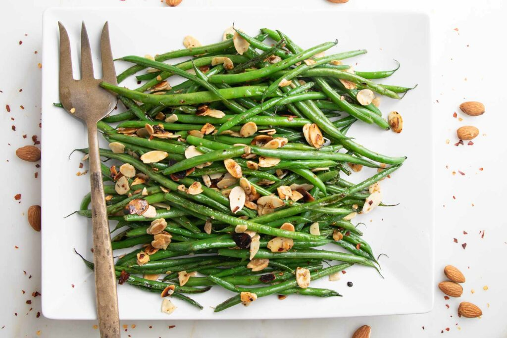 Long rectangle white platter, filled with french cut beans that are bright green, scattered with sliced almonds and sprinkled with crushed red pepper.