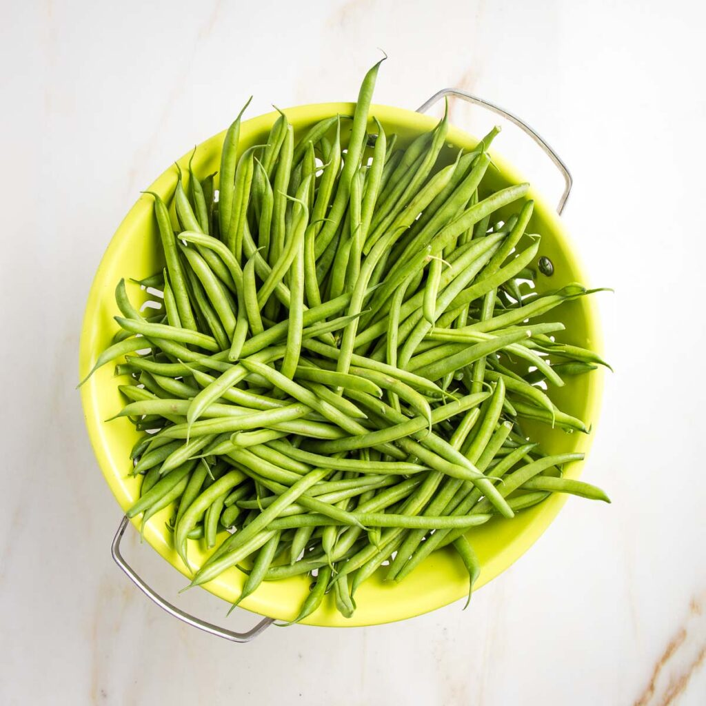 Lime green colander filled with green beans.