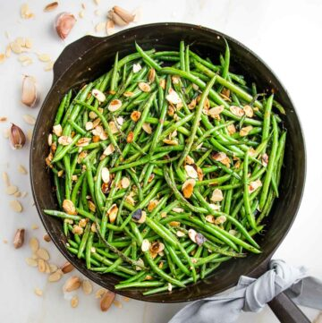 Cast iron pan filled with green beans almondine. There are almond slices, cloves of garlic and crushed red pepper scattered around the pan and a grey napkin tied around the cast iron handle.
