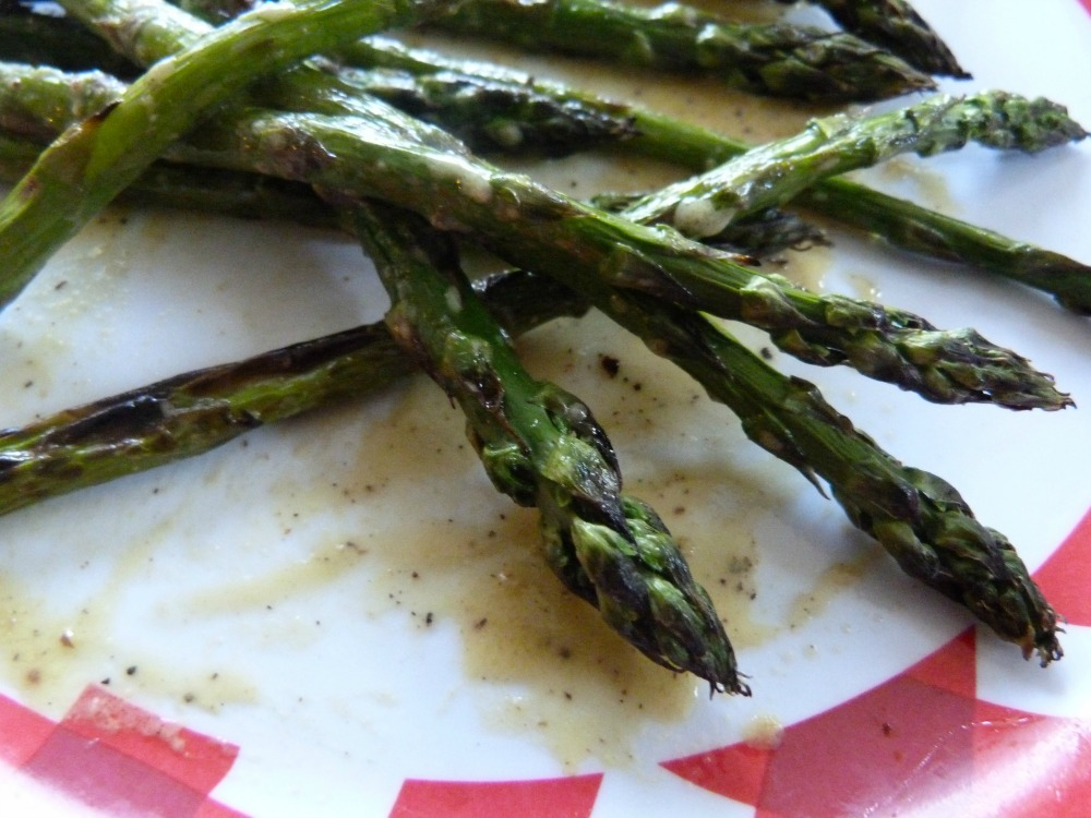 Close up of asparagus in a pool of mustard sauce.