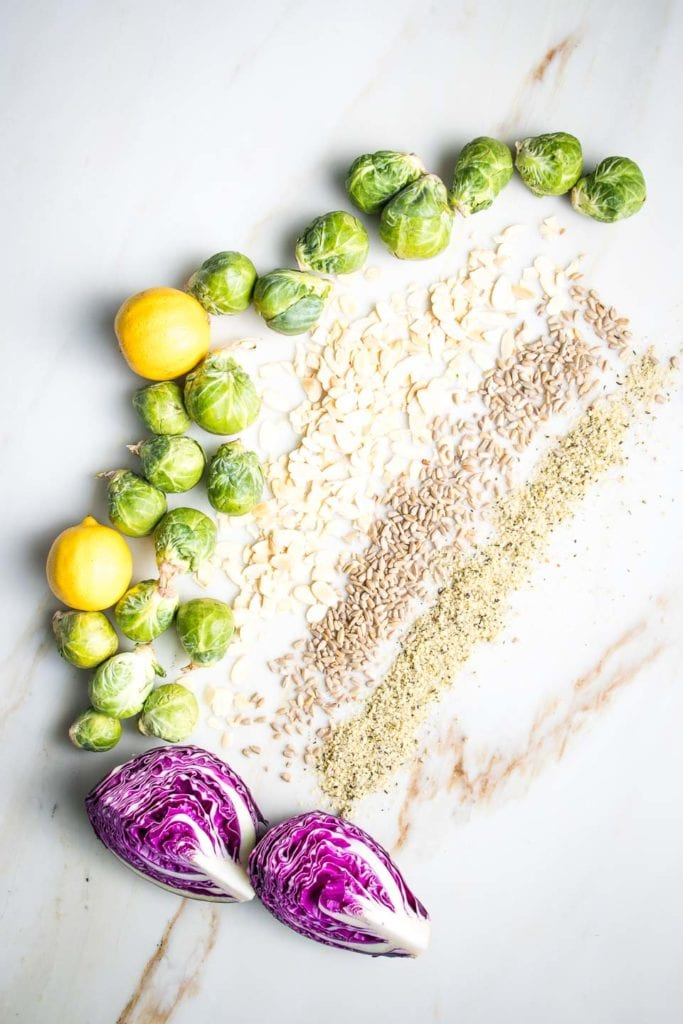 """A gorgeous display of ingredients for Shredded Brussels Sprouts Salad:  sprouts, purple cabbage and lemons arranged freeform like a giant letter """"C"""" and then stripes of scattered sliced almonds, sunflower seeds and hemp seeds on a marble countertop flecked with tan and gray abstract markings."""