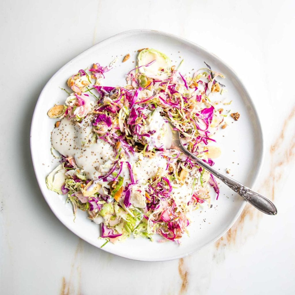 White plate with shredded brussels sprouts and cabbage, toasted nuts and seeds and a creamy dairy-free dressing.
