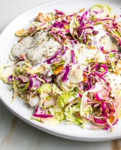 Shredded brussels sprouts and cabbage salad with creamy dairy-free dressing on a white plate, sprinkled with toasted nuts and seeds