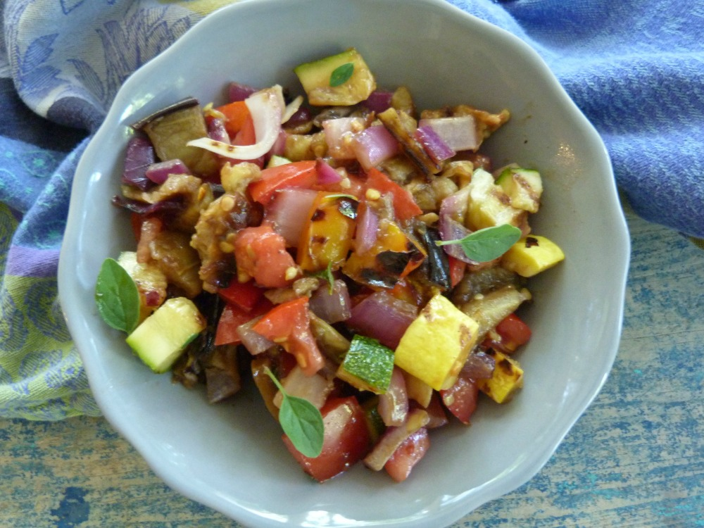Small gray bowl filled with chopped up grilled eggplant, zucchini, summer squash, peppers and chopped tomatoes.