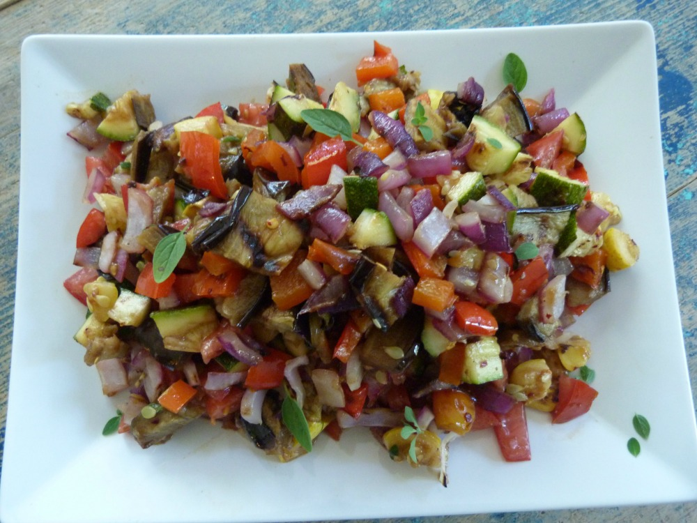 a white plate with brightly colored chopped veggies with grill marks.