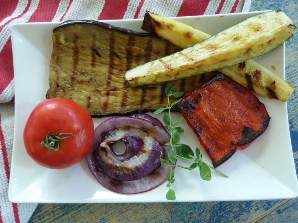 White plate with a tomato, a piece of grilled eggplant, grilled red pepper, grilled spears of summer squash and a thick slice of purple onion.