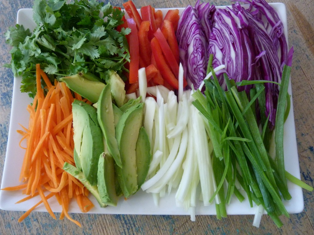 A tray of colorful julienned vegetables are ready to wrap.