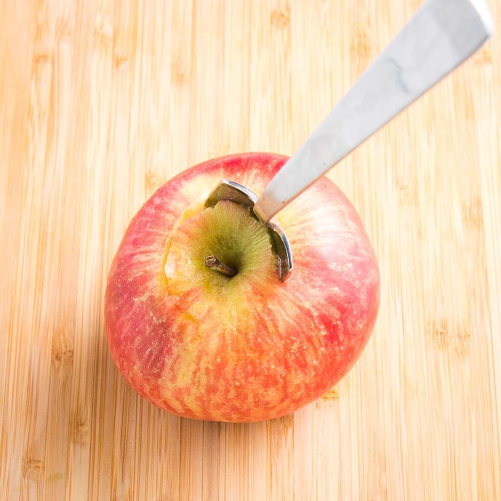 Close up of a red apple on a cutting board with a grapefruit spoon stuck into the center to scoop out the core.