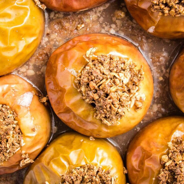 Close up of baked apples, stuffed with oatmeal in a glass pie plate.
