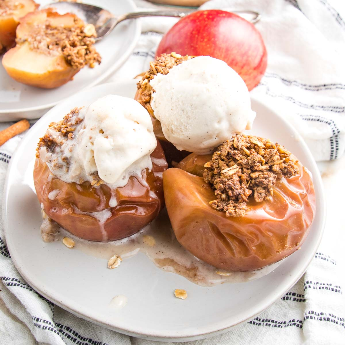 White plate with three baked apples, stuffed with cinnamon maple oats and topped with vanilla ice cream
