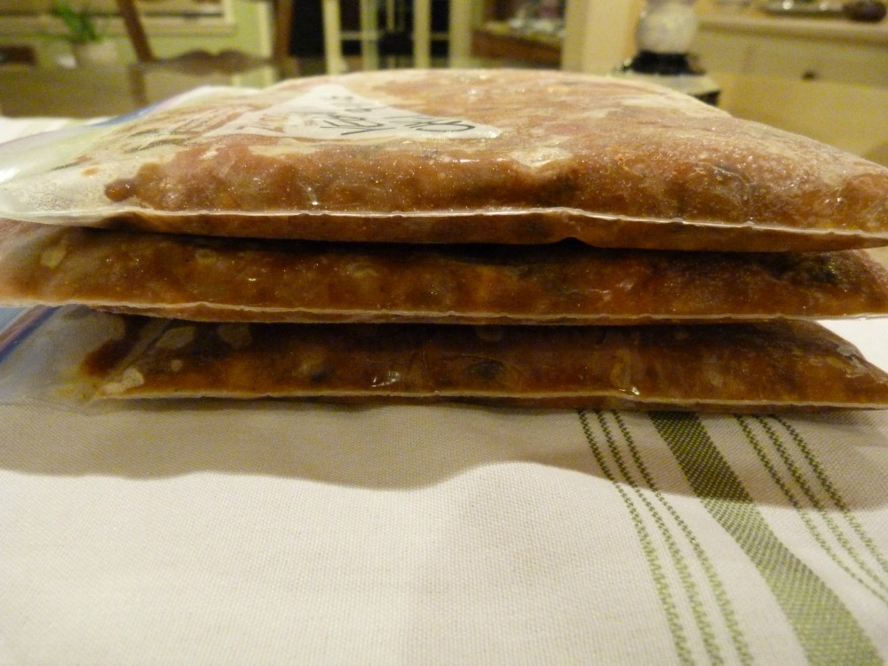 Zip top bags laying flat filled with chili to freeze.