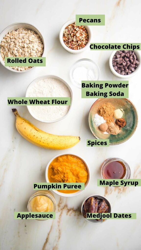 Labeled ingredients for pumpkin bread: rolled oats, whole wheat flour, pecans, chocolate chips, spices, pumpkin puree, maple syrup, applesauce, dates