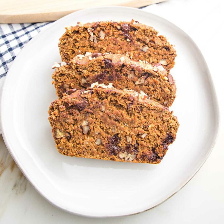 Three thick slices of pumpkin bread with chocolate chips and pecans on a white rimmed plate.