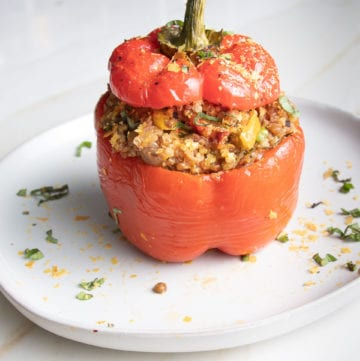 Bright red bell pepper, with the top cut off, then stuffed with quinoa, lentils and Italian spices, and roasted with the top put back on. All on a white round plate, scattered with stuffing and fresh herbs.