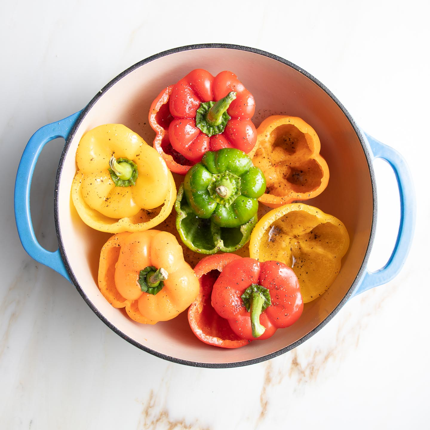 Red, orange, yellow and green bell peppers, with their tops cut off, fit tightly into a dutch oven so they stand up.