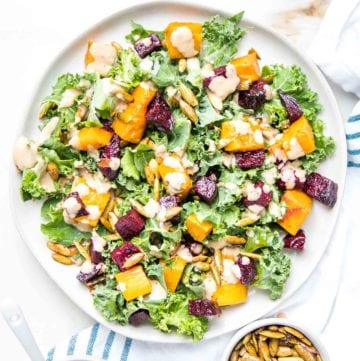 Large rimmed white plate filled with kale, roasted butternut squash and beets, toasted pumpkin seeds and a creamy balsamic dressing on top of a white tea towel with blue stripes and a small dish of extra toasted pumpkin seeds.