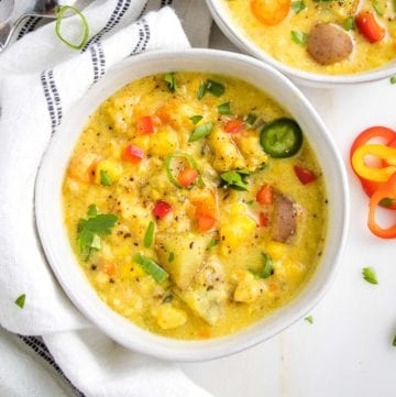 White bowl filed with thick and chunky vegetable chowder. Yellow base with colorful veggies.