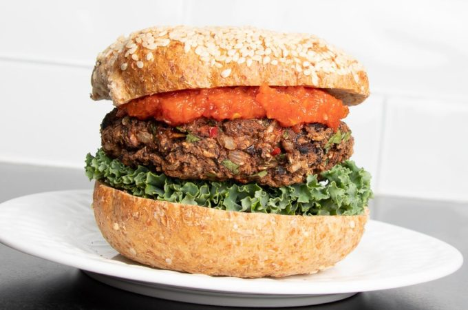 Veggie burger with red sauce, lettuce and a sesame bun on a plate.
