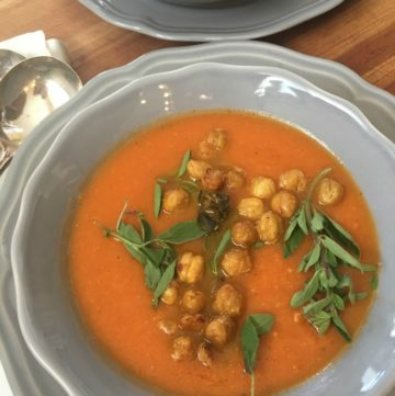 Light gray bowl filled with tomato soup, crunchy chick peas and fresh herbs.