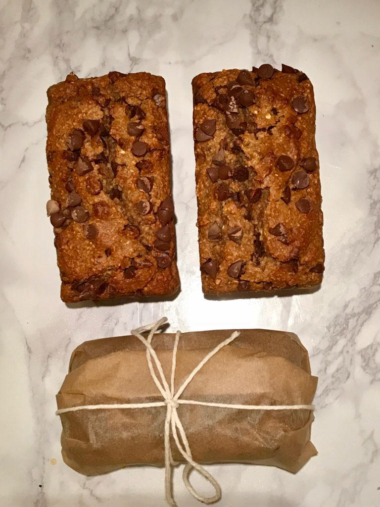 Mini loaves of chocolate chip banana bread. One is wrapped in unbleached parchment and tied with kitchen twine.