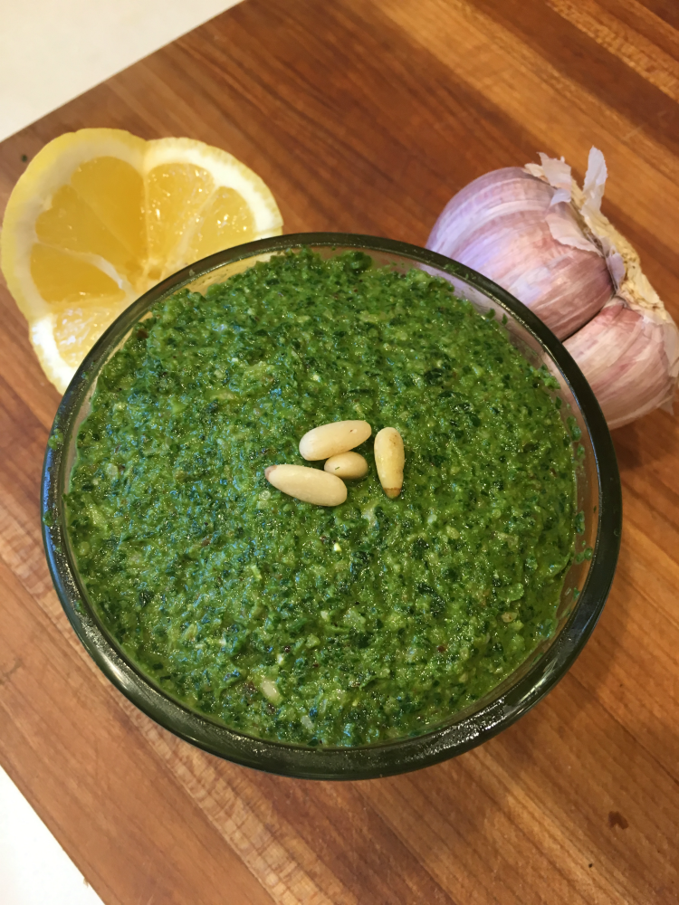 Bright green bowl of pesto with lemon garlic and pine nuts on the sides.