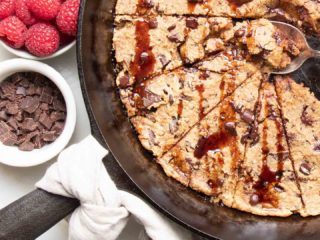 Cast iron skillet with a natural linen napkin tied around the handle, filled with chocolate chunk skillet cookies drizzled with date syrup and a spoon in the center pulling out an ooey, gooey piece. A small white dish of chocolate chunks and a dish of bright red raspberries are also in the photo.