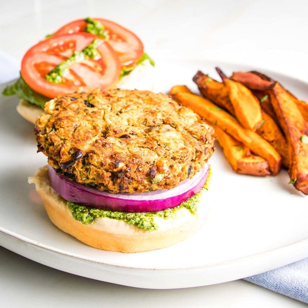 Open faced white bean veggie burger with purple onion and green arugula aioli plus lettuce and tomatoes with a side of crispy sweet potato fries.