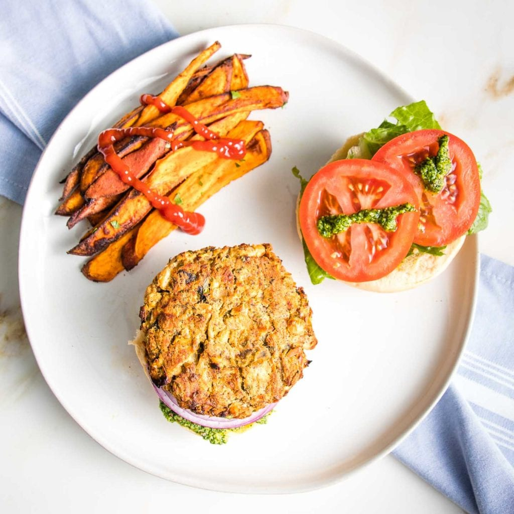 White bean burger on a bun with lettuce and tomatoes and purple onion and arugula aioli plus sweet potato fries drizzled with ketchup on a round white plate.