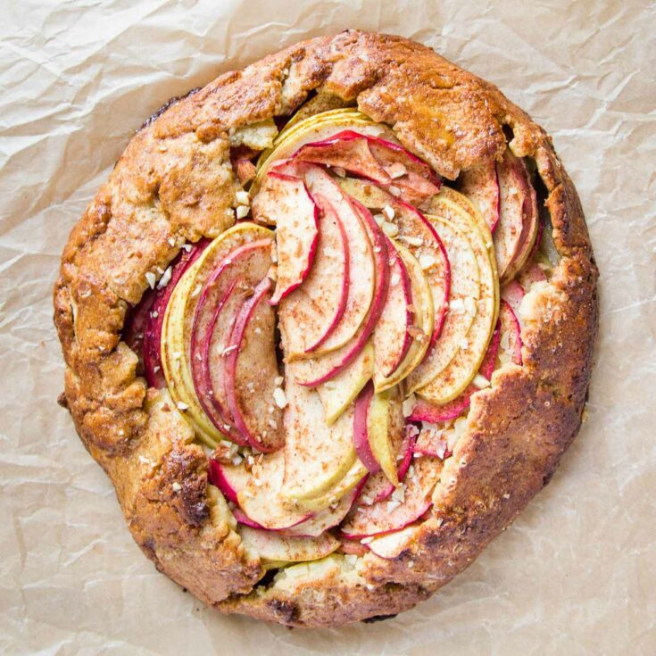 Free formed galette with a golden crust and with an assortment of green and red sliced apples, sprinkled with chopped almonds.